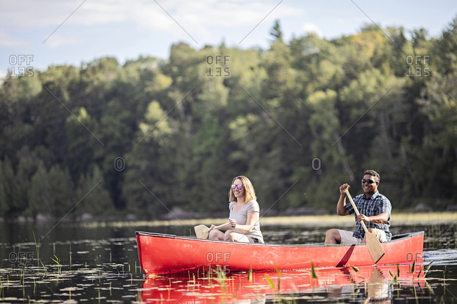 Multi racial couple paddle a red canoe on bald mountain pond, maine