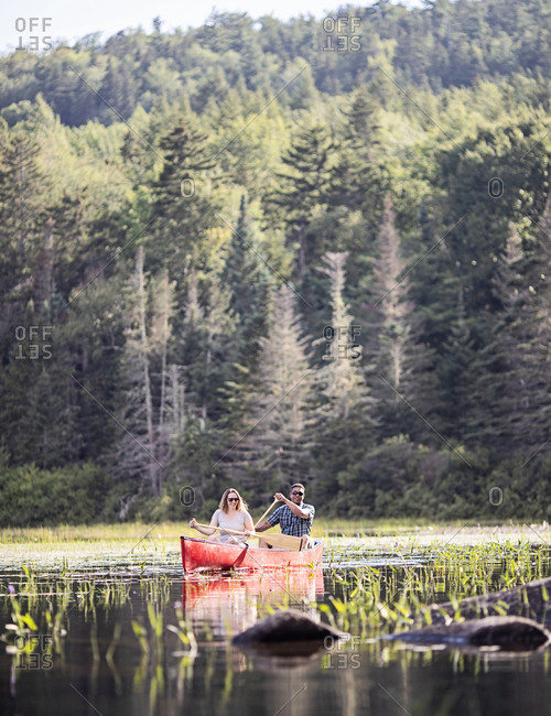 Couple, white woman and black male paddle in red canoe on lake, maine