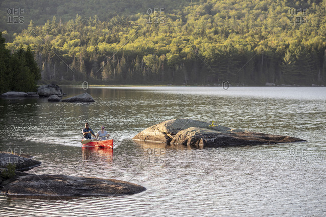 Paddlers steer canoe through rocky section on beautiful lake in maine