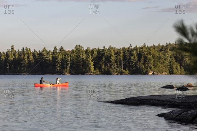 Couple paddles canoe in late afternoon on tranquil pond in maine