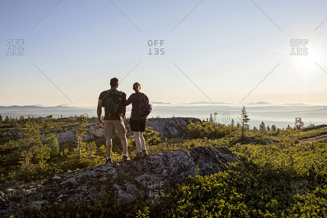 Couple stand together watching view from top of moxie bald mountain