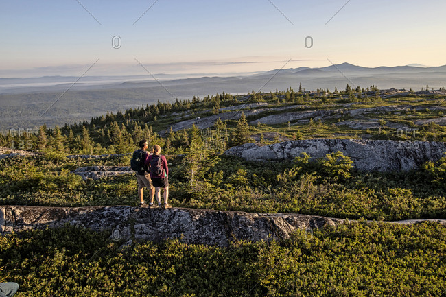 Two hikers stand on summit of mountain looking at view, appalachians