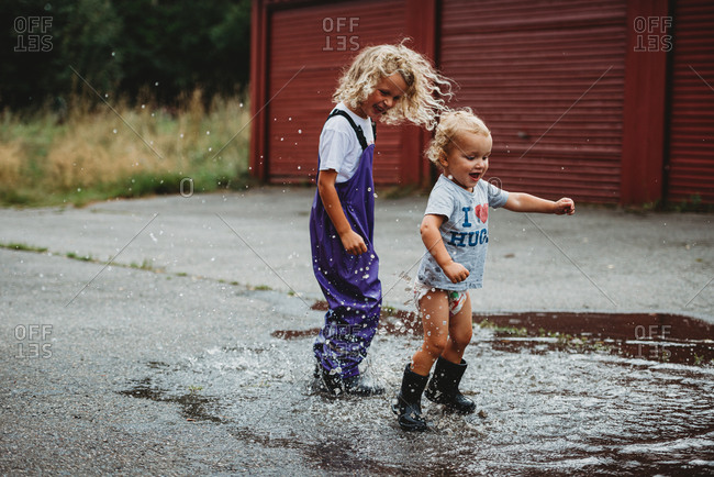Siblings boy and girl jumping in a puddle having fun and smiling