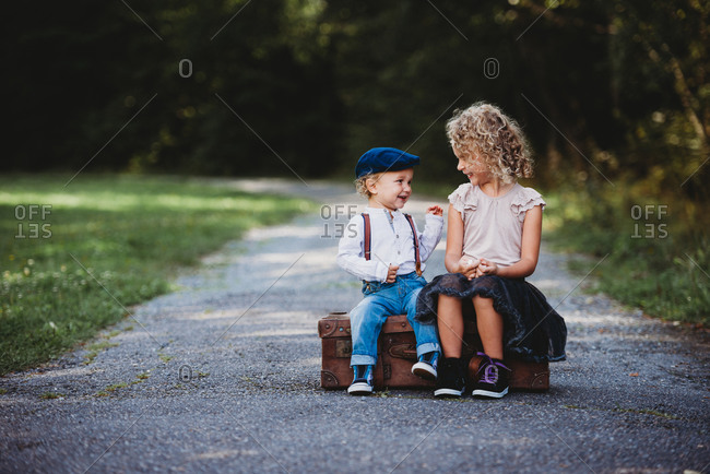 Brother and sister sitting on a vintage suitcase smiling at each other