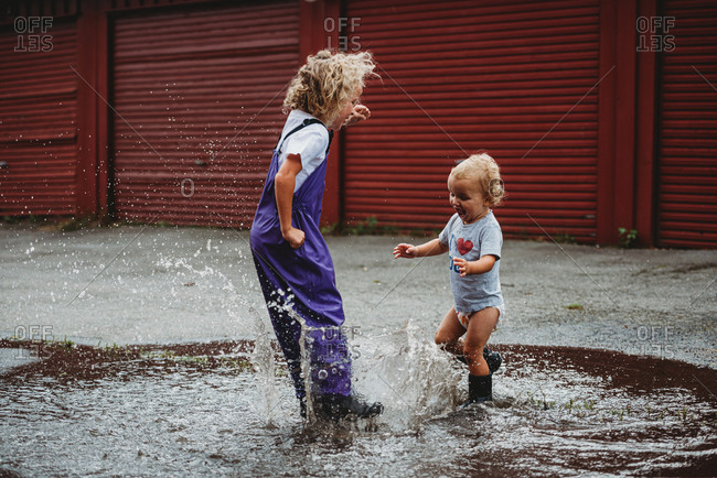 Girl and boy splashing in the water after the rain and laughing