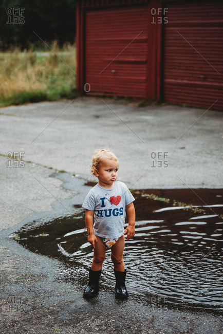 Adorable young boy pouting wearing rubber boots next to a puddle