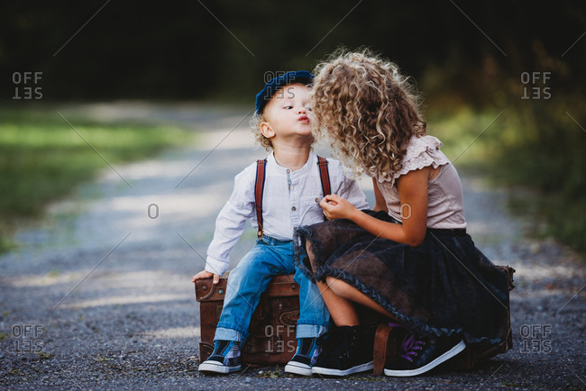 Adorable children siting on a vintage suitcase throwing a kiss