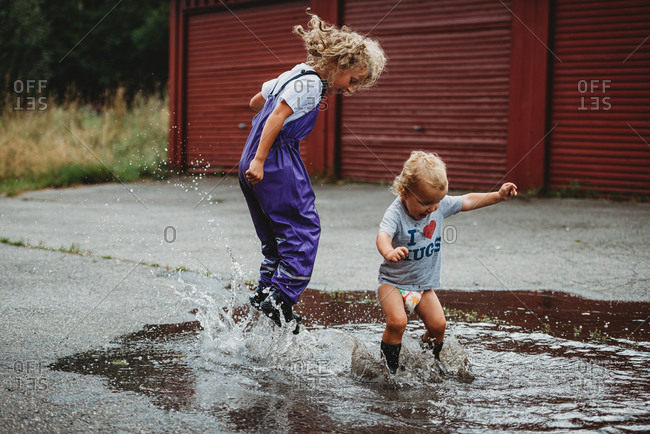 Brother and sister jumping in a big puddle having fun and laughing