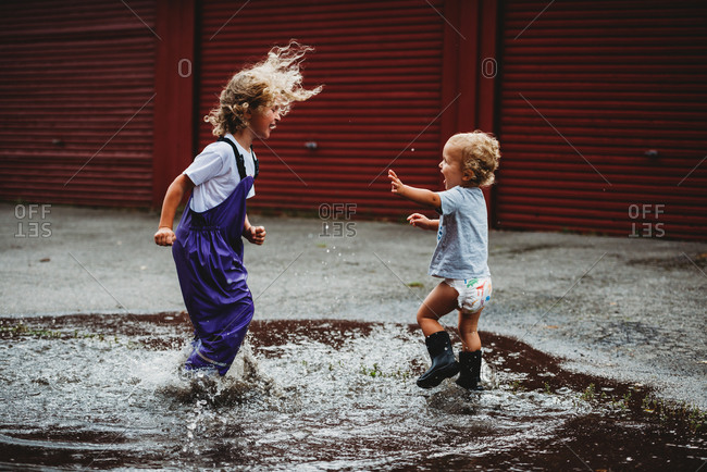Siblings boy and girl jumping in a puddle having fun