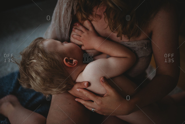 Boy breastfeeding naked with his hand on mom's breast showing skin