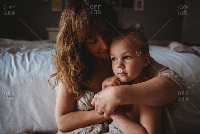 Portrait of beautiful girl and mom sitting at the end of bed hugging