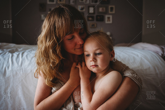 Mother with closed eyes while hugging daughter in bedroom