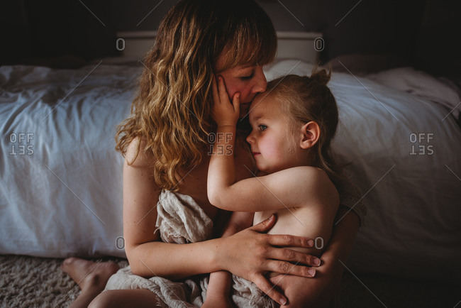 Mother kissing daughter while hugging skins to skin in bedroom