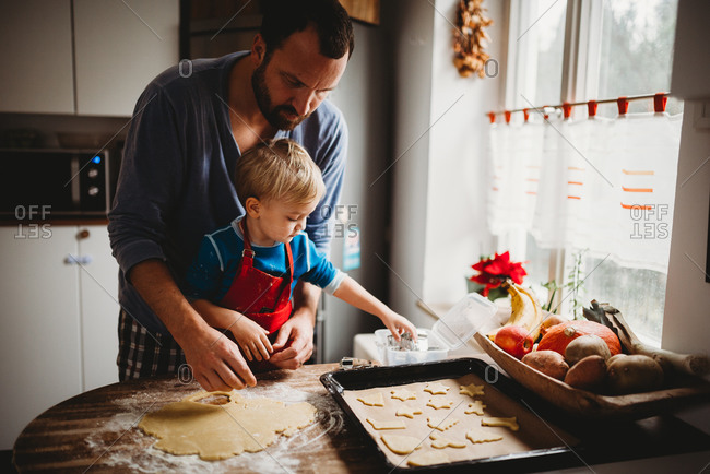 Father and son in kitchen at home baking christmas cookies in pajamas