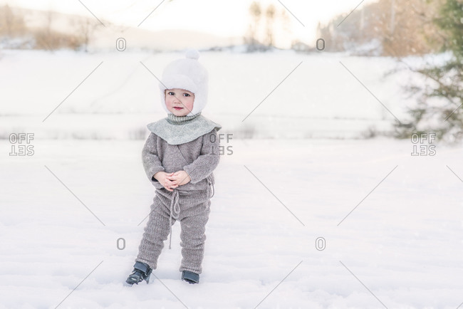 Adorable child standing in snow at farm wearing wool knitted clothes
