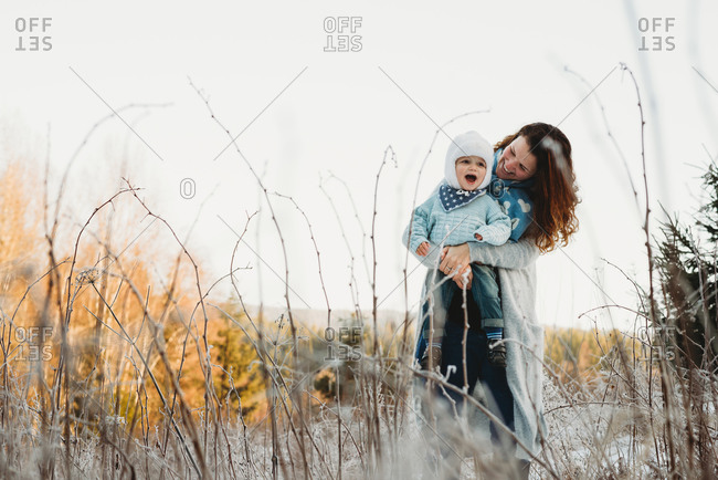 Mother holding child in arms on a sunny day in frosted field winter