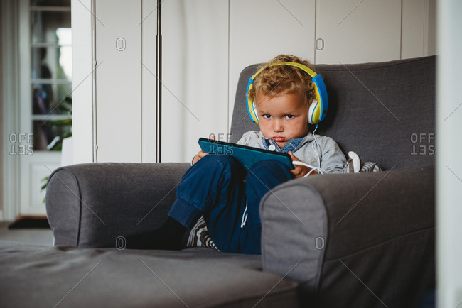 Boy pouting playing with a tablet and wearing headphones at home covid