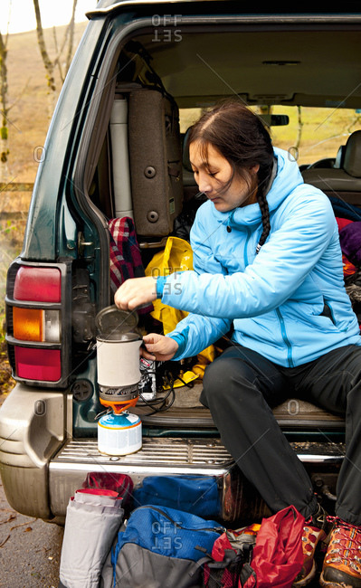 Woman boiling water on camping stove at the back of her car
