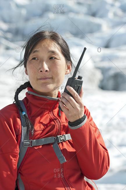 Woman using radio on vatnajokull glacier