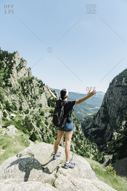 Rear view of a woman raising her hands on the top of a mountain