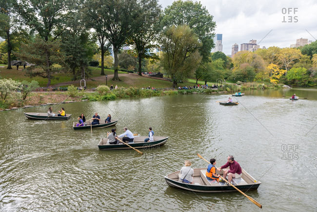 New york, ny, united states - october 18, 2014: a group of people rowing in small boats at central park lake