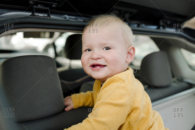 Happy baby with first teeth wearing yellow shirt standing in open suv