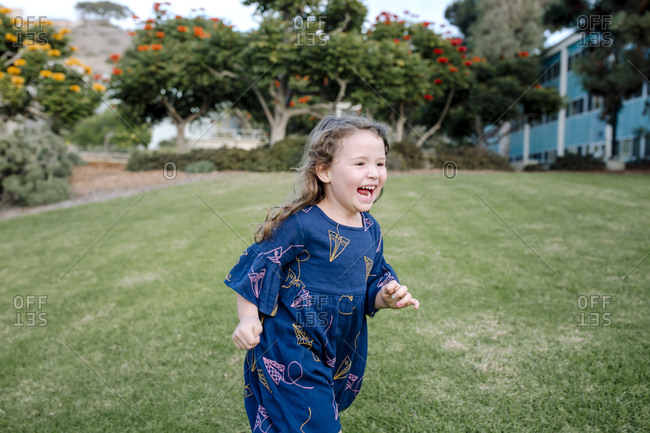 Laughing young girl running across lawn with trees in background