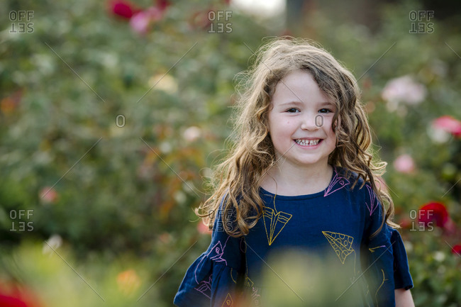 Smiling young girl with long wavy hair standing among flowers