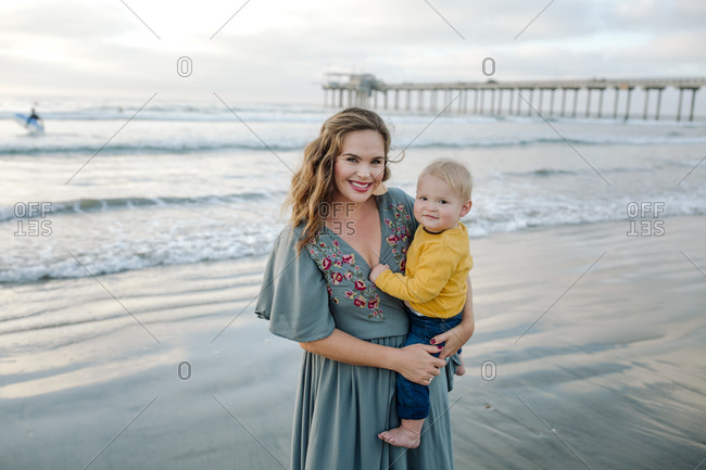 Beautiful 30 yr old mom holding baby at beach near pier