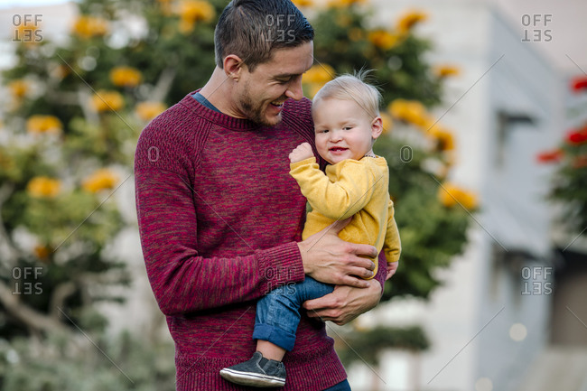 Laughing young dad holding happy blonde baby in yellow shirt