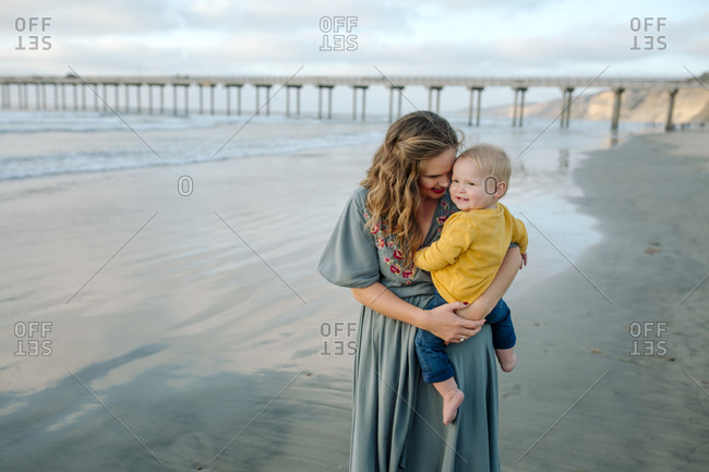 Young mother with long hair holding blonde baby at beach near pier