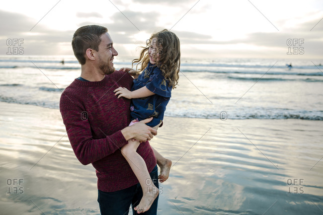 Young dad holding laughing bare-legged 3 yr old daughter at the ocean