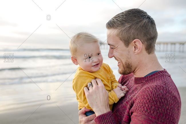 Laughing dad holding smiling baby at the ocean near scripps pier