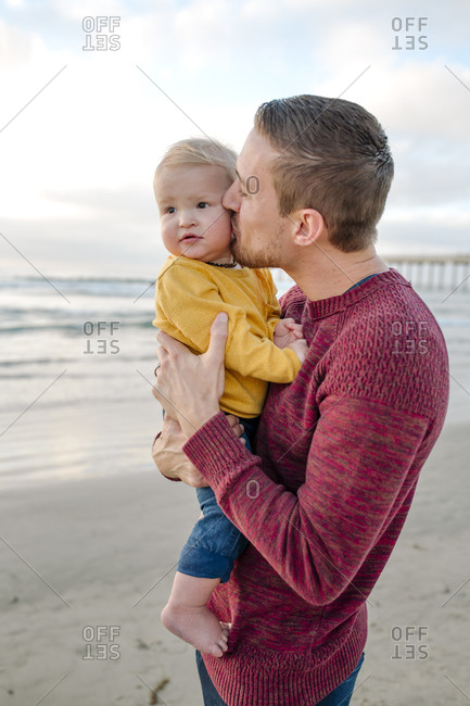 Loving dad kissing cheek of 6 month old baby at ocean near pier