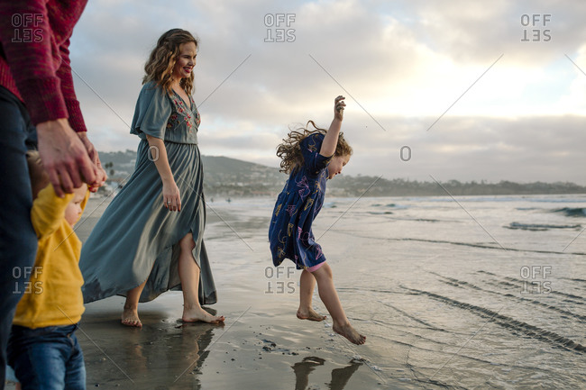 Laughing girl in blue dress jumping in ocean surf with family watching