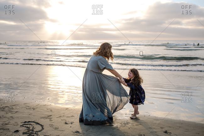 Mom in long dress playing with 3 yr old daughter on beach at sunset