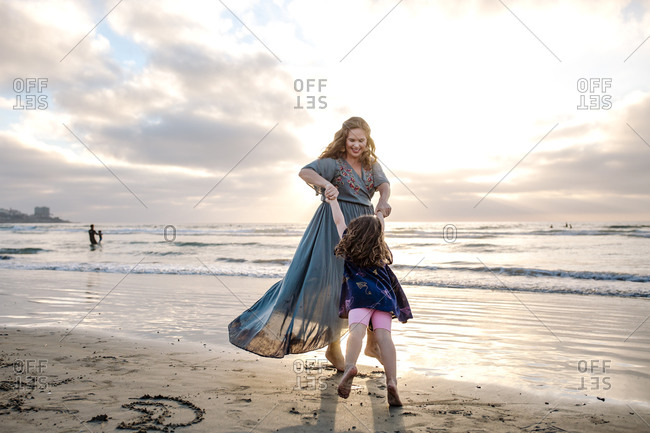 Laughing mom in dress swinging daughter by arms at beach at sunset