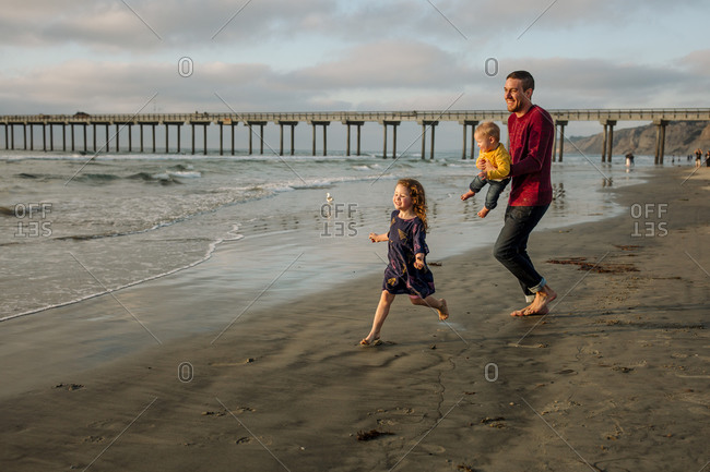 Laughing dad holding baby chases daughter on beach near pier