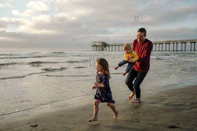 Laughing dad holding baby running on beach with daughter near pier