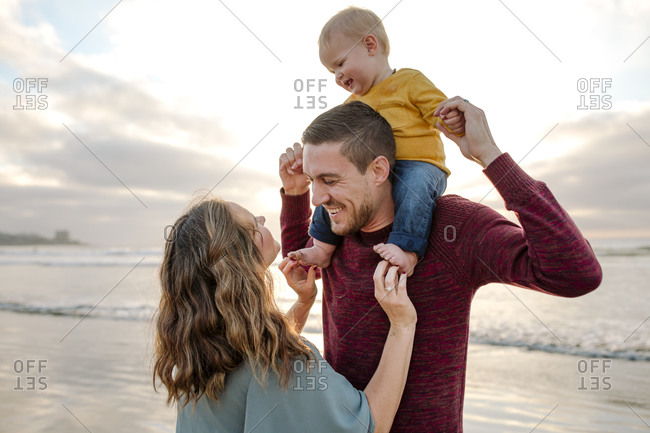 Mom tickles feet of laughing baby sitting on dad's shoulders at ocean