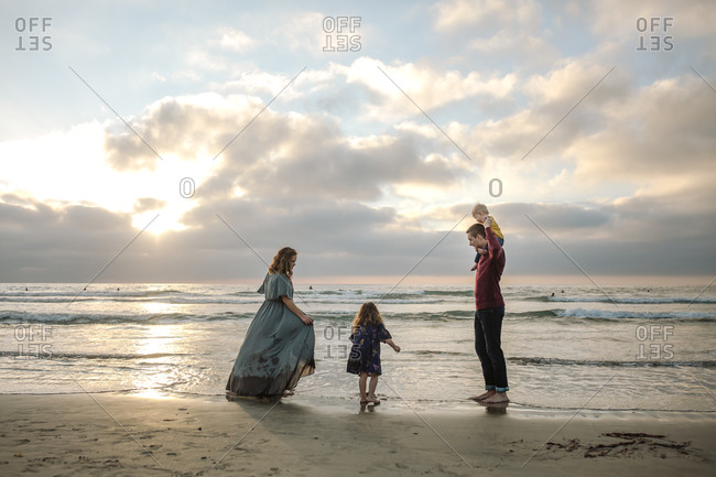 Mom in long dress at beach with husband, daughter and baby at sunset