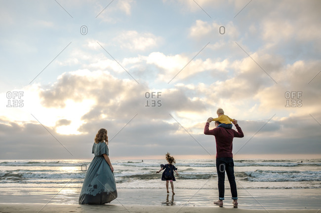 Mother in dress at ocean with husband, daughter and baby at sunset