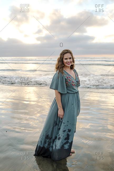 Beautiful barefoot woman in long blue dress standing on beach