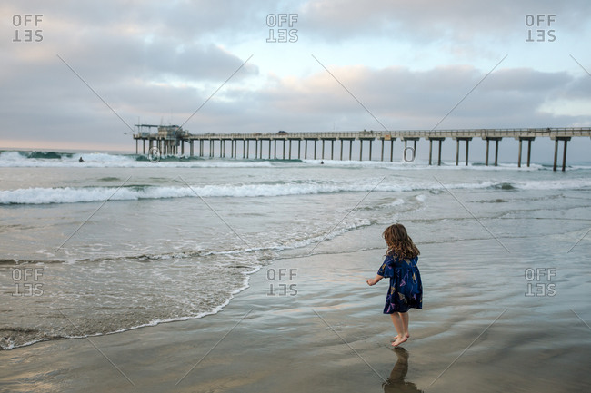 Young girl wearing dress wading in ocean surf near pier at sunset