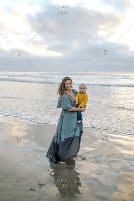 Glowing young mother in long dress standing in ocean surf holding baby