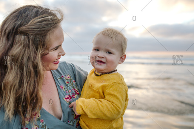 Glowing 30 yr old mom holds happy 6 mo old baby at ocean at sunset