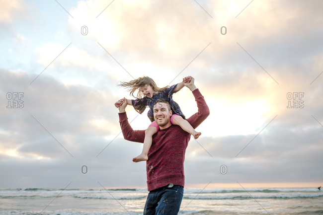 Laughing 3 yr old girl on dad's shoulders by ocean at sunset
