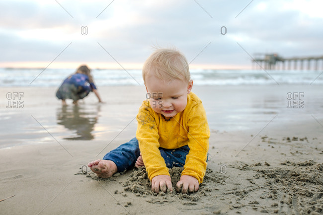 6 mo old in yellow shirt playing in at beach with sister near pier