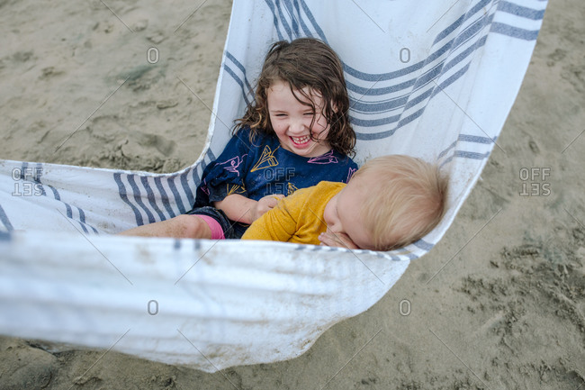 Laughing girl and little brother in towel hammock at the beach