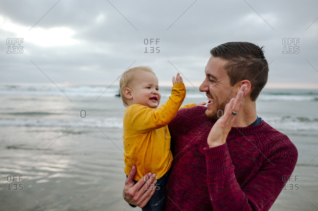 Laughing 30 yr old father holding baby at the ocean giving high-fives